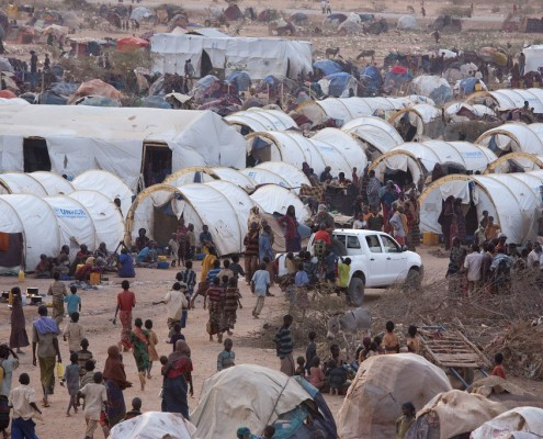 Ethiopia, Ethiopie, Dollo Ado, Dolo Ado, Aug 2011 Dolo Ado transit, zo heet het tijdelijke opvangterrein in het Ethiopische grensgebied met Somalie. Zo'n 14.000 vluchtelingen wachten in het transit centrum totdat ze een tent krijgen toegewezen in een van de drie overvolle offici'le vluchtelingenkampen 80 kilometer landinwaarts. En iedere dag komen hier nog eens 250 Somalische vluchtelingen bij. ÔDolo Ado transitÕ is niet ingericht om vluchtelingen voor langere tijd op te vangen. Het terrein is dan ook een semi-geordende chaos. Overal staan zelfgemaakte hutjes van stokken, sprokkelhout, doeken en plastic zeil, met weer verderop tientallen witte tenten om mensen toch enige vorm van onderdak te bieden. Een vierde vluchtelingenkamp met een capaciteit voor 40.000 vluchtelingen gaat op 3 augustus open. Een ambitieuze planning, als je bedenkt dat de plek waar dit Heloweyn kamp moet gaan komen vooralsnog een volstrekt kale, rotsachtige vlakte is. ÒDe uitdaging zit 'm in het bouwen van de wc'sÓ, vertelt hulpverlener Abdirashid van Save the Children. ÒDe grond is keihard, dus er zijn drilboren nodig om de gaten te graven. Een race tegen de klok, want Dolo transit barst uit z'n voegen. Maar zolang er geen wc's zijn, kan het kamp niet open.  De Samenwerkende Hulporganisaties (SHO) voeren deze week actie voor de slachtoffers van de droogte in de Hoorn van Afrika. Meer dan 10 miljoen inwoners van Ethiopie, Somalie, en Kenia kampen met ernstig voedselgebrek door droogte, mislukte oogsten, stervend vee en hoge voedselprijzen.  Om een einde te maken aan de hongersnood is volgens de FAO, de voedsel- en landbouworganisatie van de Verenigde Naties, 1,1 miljard euro nodig. De eerste week van augustus is door de SHO uitgeroepen tot de ÔWeek voor de HoornÕ. Bedrijven en particulieren voeren actie om zoveel mogelijk geld in te zamelen voor Giro 555. Foto: Petterik Wiggers/Hollandse Hoogte