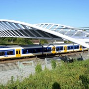 Foot-bicycle-bridge_over_the_railway_in_Houten_with_Sprinter_train_of_NS_-_panoramio